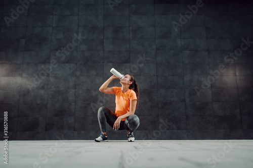 Charming fit caucasian sportswoman in shape dressed in active wear crouching and drinking water Canvas-taulu