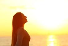 Woman Breaths Fresh Air At Sunset On The Beach