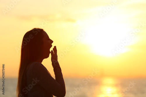 Photo  Tired woman yawning at sunset on the beach