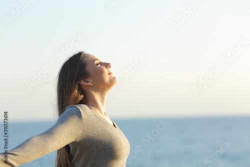 Obraz Relaxed woman breathing fresh air on a beach - fototapety do salonu