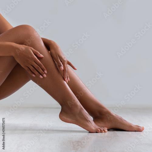 Obraz Black woman touching silky skin on her legs - fototapety do salonu