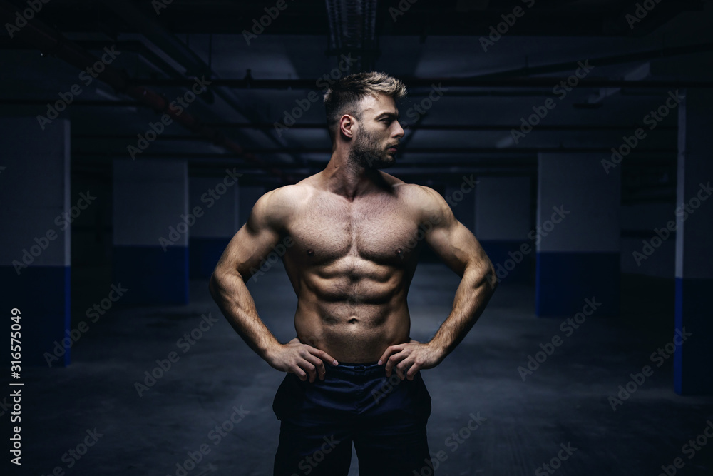 Fototapeta Young handsome shirtless Caucasian muscular sportsman standing with hands on hips in garage at night and looking away. Urban life concept.