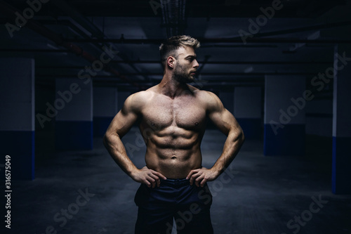 Fotografía Young handsome shirtless Caucasian muscular sportsman standing with hands on hips in garage at night and looking away