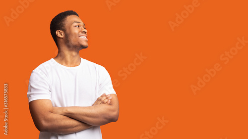 Cuadros en Lienzo Smiling black man profile portrait on orange background