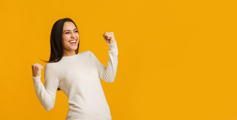 Euphoric brunette woman celebrating success with raised fists over yellow bac...
