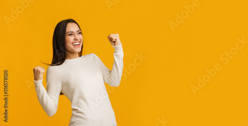 Euphoric brunette woman celebrating success with raised fists over yellow backgr Canvas Print