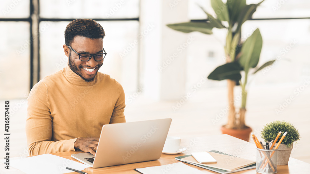 Fototapeta Headshot of handsome black guy using laptop
