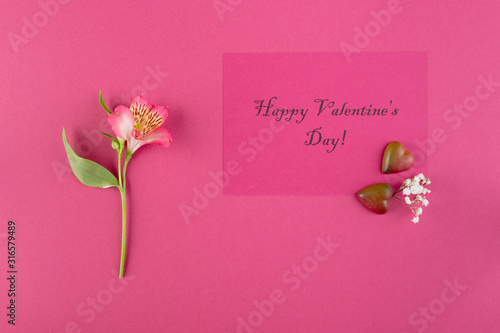 Happy Valentine's day greeting card concept. Alstroemeria flowers and the inscription Shchoslivogo Valentine's Day on a pink paper background