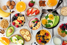Healthy Breakfast Table Scene With Fruit, Yogurts, Oatmeal, Smoothie Bowl, Cereal, Nutritious Toasts And Egg Skillet. Top View Over A White Wood Background.