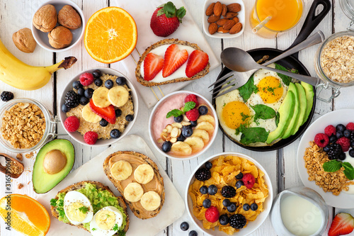 Fototapeta Healthy breakfast table scene with fruit, yogurts, oatmeal, smoothie bowl, cereal, nutritious toasts and egg skillet. Top view over a white wood background. obraz