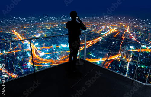 Obraz Businessman standing using smart phone in modern space watching city night view.Business Wireless network and Connection technology concept. - fototapety do salonu
