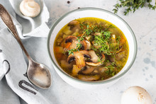 Homemade Thick Vegetarian Mushroom Soup With Barley And Vegetables With Herbs In A Ceramic Bowl On A Light Grey Stone Background. Delicious Cozy First Course, Comfort Food.