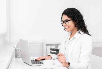 Latin woman holding credit card using laptop