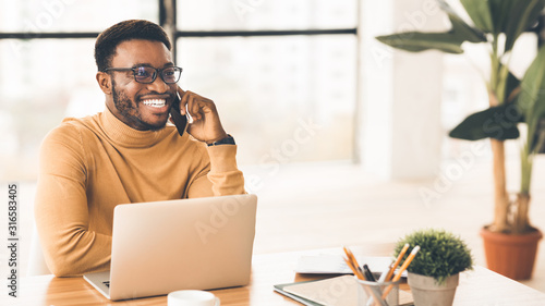 Obraz Black businessman talking on cell phone at office - fototapety do salonu