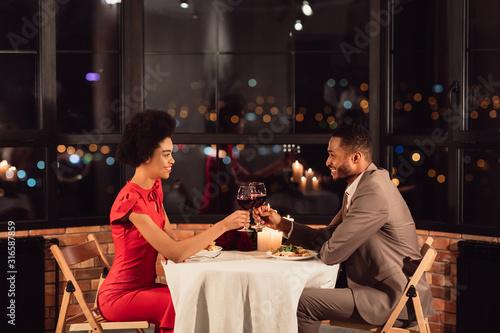 Obraz Couple Clinking Glasses Drinking Wine Celebrating Valentine's Day In Restaurant - fototapety do salonu
