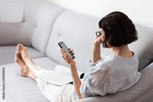 Fotografie, Tablou Middle-aged brunette woman with glasses on the gray sofa use smartphone, soft focus comfort concept of loneliness