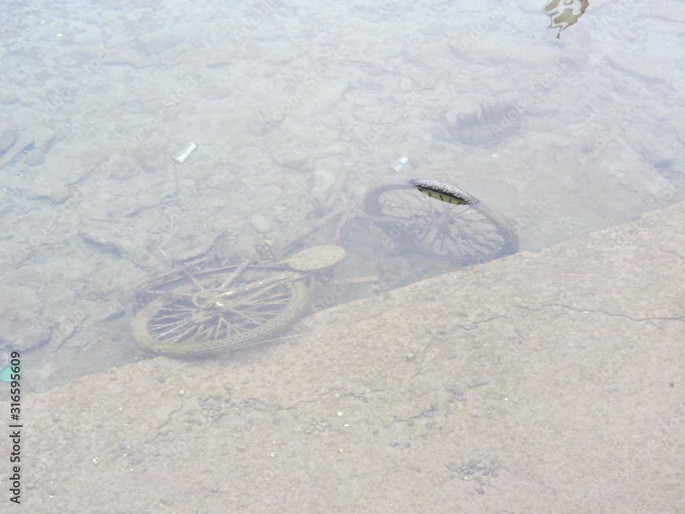 Fototapeta Porzucony stary, zardzewiały rower na dnie rzeki