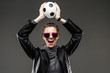 Leinwanddruck Bild - sports betting concept. girl in a leather jacket and gray sweatshirt with glasses holds the ball over her head on a dark gray background