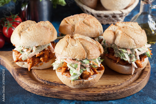Photo Pulled chicken sandwich with salad and bbq sauce