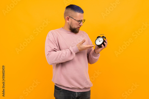 Obraz Young strong man with short black hair and glasses holds alarm clock and smiles - fototapety do salonu