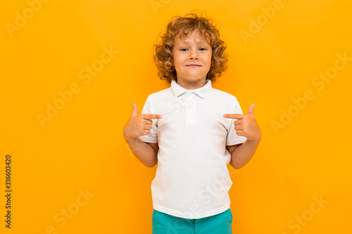 Obraz Little boy with curly hair in colourful t-shirt and shorts shows thumbs for himself isolated on yellow background - fototapety do salonu