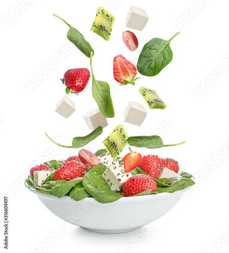 Fototapeta Bowl with fresh salad and falling ingredients on white background obraz