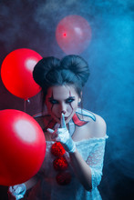 Young Modern Woman Clown Old Costume Creative Bright Art Makeup Hairstyle Two Bagels Bun. Evil Eyes Mad White Lenses. Backdrop Black Gothic Mystery Room Balloon. Finger On Lips Sign Silence. Hide Seek