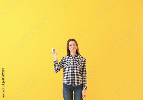 Young woman with air conditioner remote control on color background Wallpaper Mural