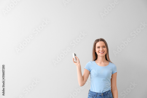 Photo Young woman with air conditioner remote control on white background