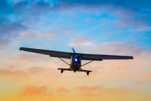 Shot Of A Silhouetted,  Unidentifiable Private Aircraft On Final For Landing As The Sun Sets.