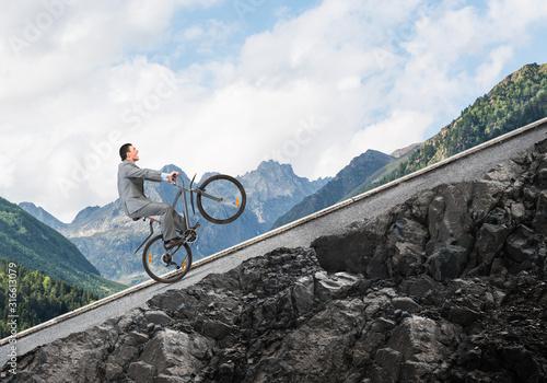 Fotografie, Obraz Businessman riding downhill by bike
