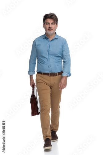 Zmotywowany przypadkowy mężczyzna trzyma teczkę i chodzi