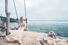 Girl Relaxing On Beach Swings On Bali