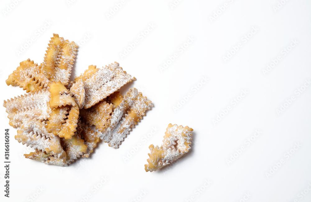 Fototapeta Vista dall'alto di dolci tradizionali di carnevale fatti in casa: chiacchiere su sfondo bianco.