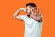 canvas print picture - Stinky smell. Side view of confused brunette man with beard in white t-shirt holding breath with fingers on nose, disgusted by bad odor fart, gesturing stop. studio shot isolated on orange background