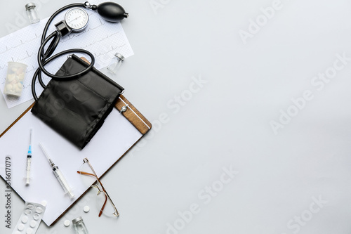 Composition with sphygmomanometer, clipboard and pills on light background Canvas Print