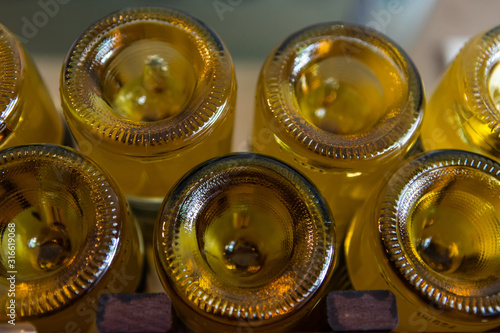Fototapeta a lot of amber color glass empty wine bottles bottom close up view, with a punt