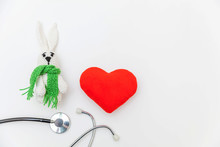 Simply Minimal Design Toy Bunny Red Heart And Medicine Equipment Stethoscope Isolated On White Background. Health Care Children Doctor Concept. Pediatrician Symbol. Flat Lay, Top View Copy Space