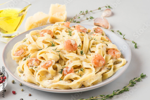Italian pasta fettuccine or tagliatelle in a creamy sauce with shrimps in a plat Canvas Print