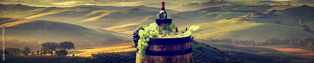 Fototapeta Red wine bottle and wine glass on wodden barrel. Beautiful Tuscany background