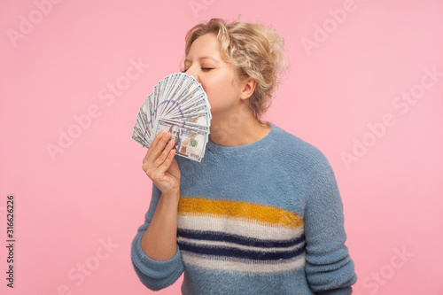 Portrait of pleased happy woman with curly hair in warm sweater smelling dollar banknotes and closing eyes from pleasure and satisfaction, greed for money Fototapeta