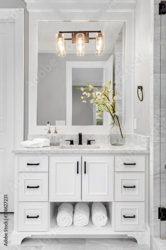 Fotografía Bathroom in traditional style luxury home with vanity, mirror, sink, and tile fl