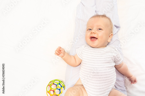 Photo Happy little baby lay on the bed smile and babbling laughing