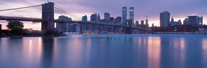 This is the Brooklyn Bridge over the East River with the Manhattan skyline at dusk. The lights of the city are starting to come on.