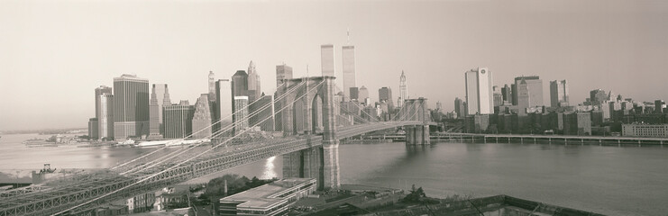 This is the Brooklyn Bridge over the East River. The Manhattan skyline is behind it at sunrise.