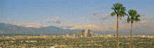 This Is A Clear View Of Downtown Los Angeles. It Shows Mount Baldy And Two Palm Trees From Baldwin Hills At Sunset. There Is Snow On The Mountains.