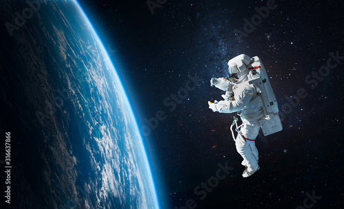 Fototapeta Astronaut in the outer space over the planet Earth