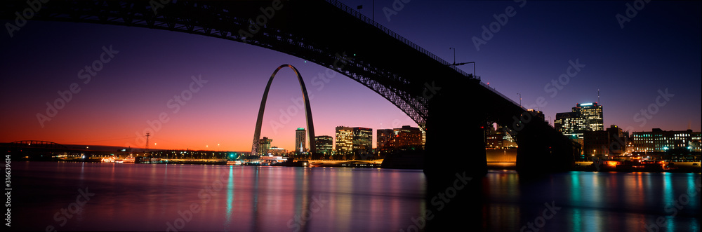 Fototapeta This is the skyline and Arch at sunset. Above it is the Eads Bridge along the Mississippi River. There is a purple cast in the sunset sky.