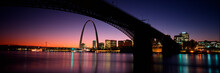 This Is The Skyline And Arch At Sunset. Above It Is The Eads Bridge Along The Mississippi River. There Is A Purple Cast In The Sunset Sky.