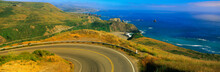 This Is Route 1 Also Known As The Pacific Coast Highway. The Road Curves Around A Bend To The Left And Drops Down Overlooking The Ocean. The Rocky Hillside Is Also Seen Next To The Ocean.